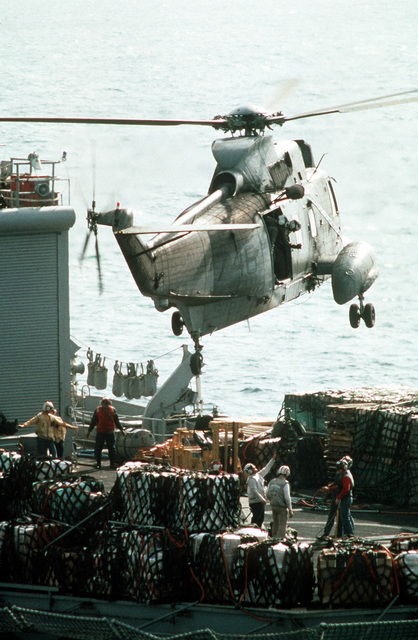 An SH-3H Sea King helicopter hovers over the flight deck of the combat stores ship USS NIAGARA FALLS (AFS-3) while several bundles are hoisted aboard during Operation Desert Storm