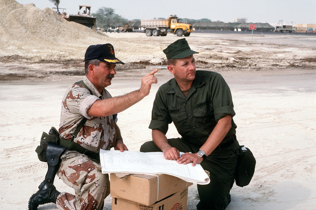 CAPT. Mel Hamm, left, commander, Fleet Hospital Operations and Training Command, and LT. Vic Modeer of Reserve Naval Construction Battalion Hospital Unit 22 discuss the construction of Fleet Hospital Six during Operation Desert Shield