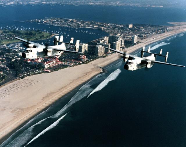 Copy negative of a pair of US Navy (USN) C-2A Greyhound, Fleet Logistics Support Squadron 30 (VRC-30), Providers, Naval Air Station North Island (NASNI), California (CA), in flight by the Hotel Del Coronado at Coronado, CA