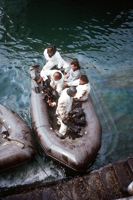 Explosive ordnance disposal (EOD) divers board an inflatable boat as they prepare to head out into the harbor to search for Iraqi mines. U.S. and coalition EOD units are clearing mines and other ordnance from Kuwait's harbors following Operation Desert Storm