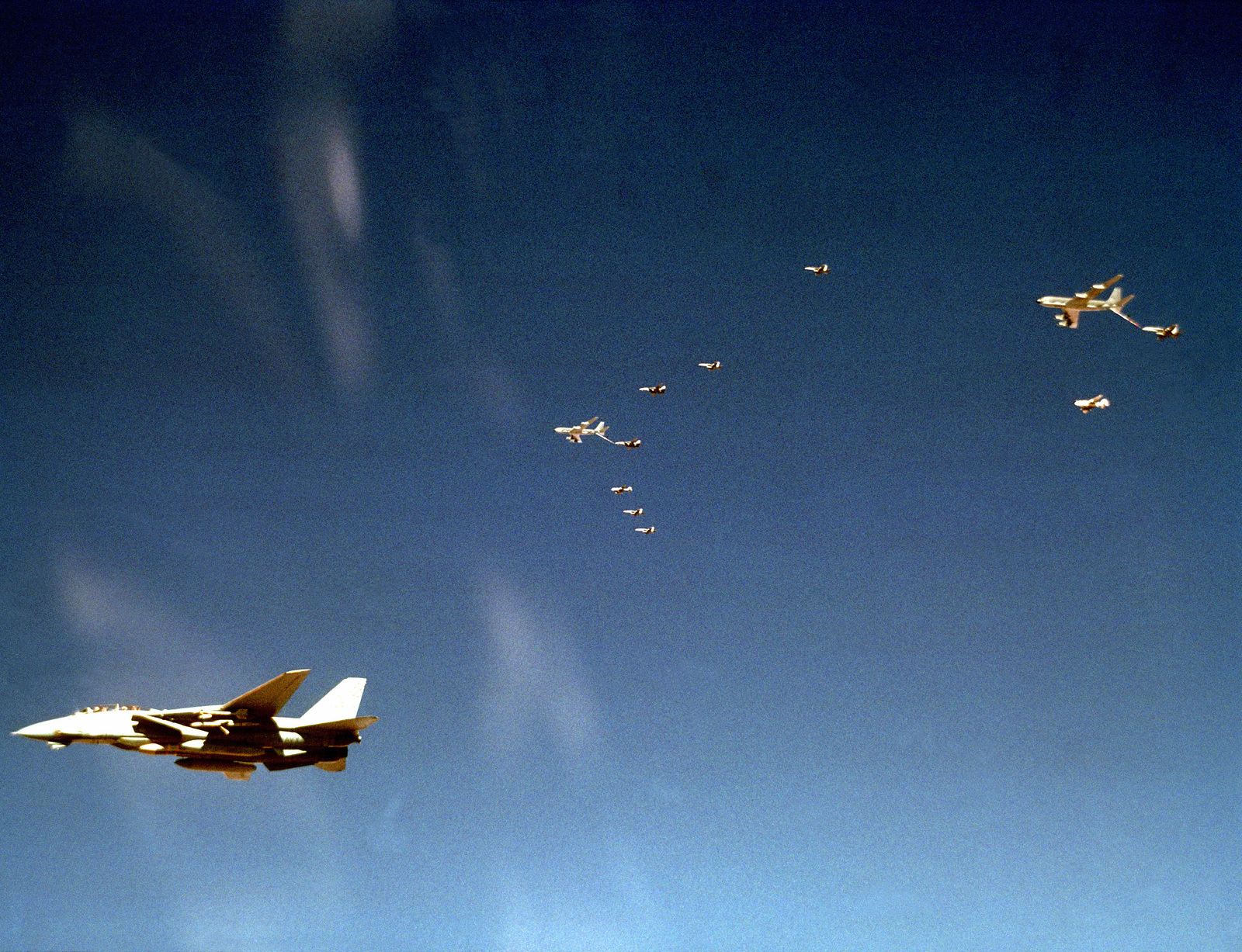 F/A-18 Hornet and A-6E Intruder aircraft from Carrier Air Wing 1 (CVW-1) conduct an in-flight refueling with a pair of U.S. Air Force KC-135 Stratotanker aircraft while en route to their target during Operation Desert Storm. A Fighter Squadron 33 (VF-33) F-14A Tomcat aircraft, also from CVW-1, is in the foreground. CVW-1 is embarked aboard the aircraft carrier USS AMERICA (CV 66).
