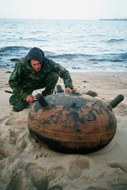 Machinist's Mate 2nd Class Roy Hunt of Explosive Ordnance Disposal (EOD) Detachment 6 examines an Iraqi contact mine that washed ashore following Operation Desert Storm