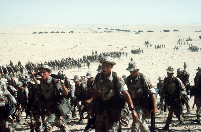 Marines of the 1ST Marine Expeditionary Force (1ST MEF) move across the Saudi desert back to their camp following a training exercise during Operation Desert Storm