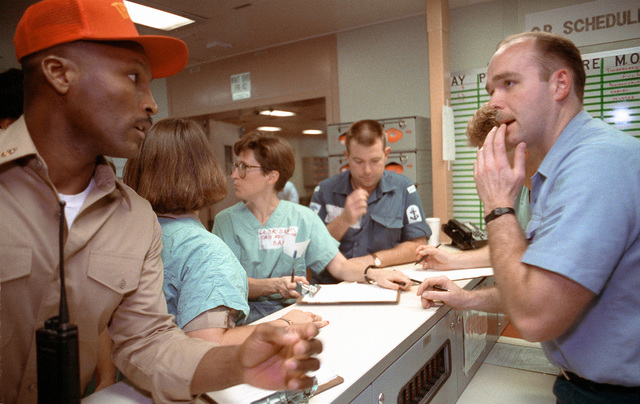 Medical personnel coordinate information at a scheduling station aboard the hospital ship USNS COMFORT (T-AH-20) while the vessel is deployed to the Persian Gulf during Operation Desert Storm