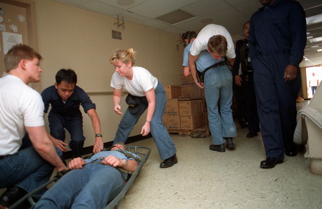 Medical personnel move simulated casualties during a drill aboard the hospital ship USNS COMFORT (T-AH-20). The vessel is deployed to the Persian Gulf during Operation Desert Storm