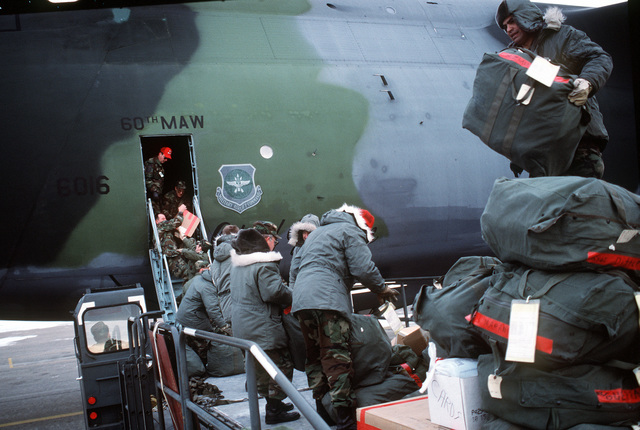 Members of the 42nd Aerial Port Squadron load baggage on a C-5 Galaxy aircraft bound for Operation Desert Storm. The C-5, from the 60th Military Airlift Wing, Travis Air Force Base, Calif., will also take on passengers before continuing east
