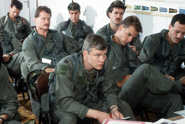 Members of the 614th Tactical Fighter Squadron listen during a briefing on the first daylight attack of Operation Desert Storm.