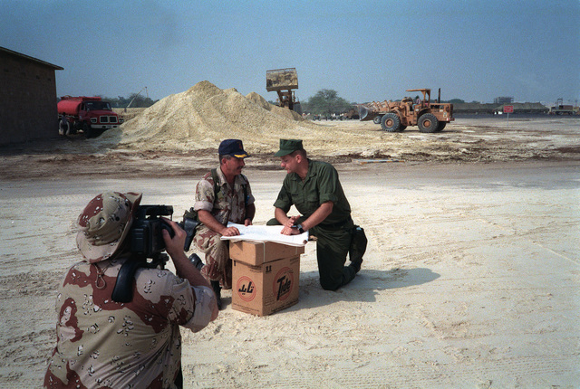 Photographer's mate 2nd Class Milton Savage, foreground, videotapes CAPT. Mel Hamm, left, commander, Fleet Hospital Operations and Training Command, and LT. Vic Modeer of Reserve Naval Construction Battalion Hospital Unit 22 as they discuss the construction of Fleet Hospital Six during Operation Desert Shield