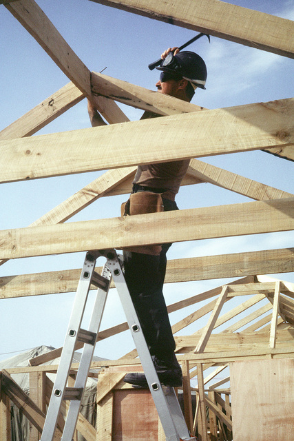 Seabee Floyd B. Jeffreys of Naval Mobile Construction Battalion 74 constructs a tent frame in a Marine camp which is being built during Operation Desert Storm. Exact Date Shot Unknown