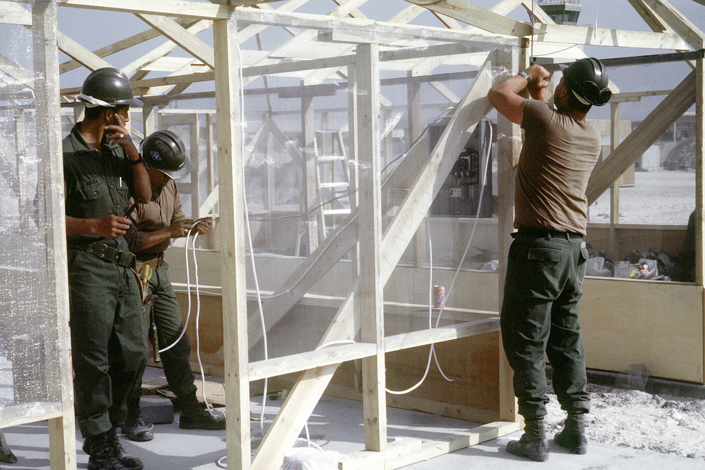 Seabees of Naval Mobile Construction Battalion 74 install electrical wiring in a tent frame in a Marine camp which is being built during Operation Desert Storm. Exact Date Shot Unknown