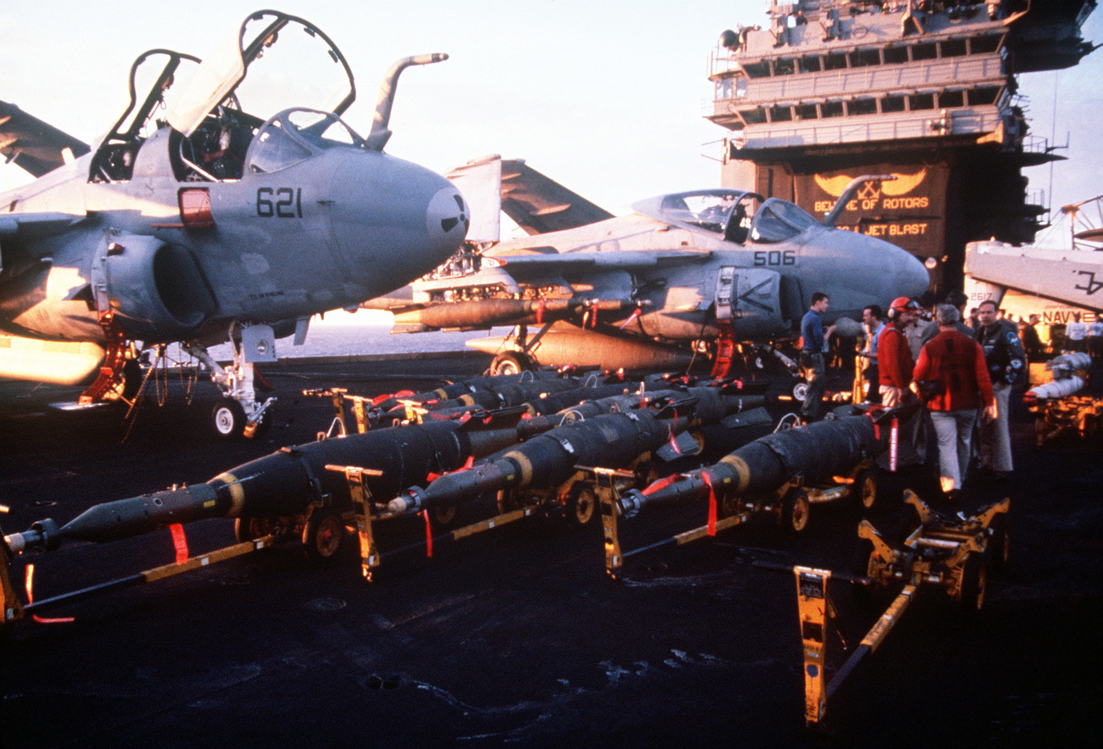 Several GBU-16B/B Paveway II laser-guided bombs rest on bomb skids on the flight deck of the aircraft carrier USS JOHN F. KENNEDY (CV-67) during Operation Desert Storm. A Tactical Electronic Warfare Squadron 130 (VAQ-130) EA-6B Prowler aircraft, left, and an Attack Squadron 75 (VA-75) A-6E Intruder aircraft are in the background