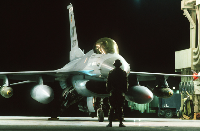 SGT. Ken Mahaley, crew chief, 17th Avionics Squadron, launches an F-16C Fighting Falcon fighter aircraft of the 363rd Tactical Fighter Wing, Shaw Air Force Base, S.C., during the first wave of the air attack on Iraq in support of Operation Desert Storm. The Falcon is armed with Mark 84 2,000-pound bombs mounted under its wings.