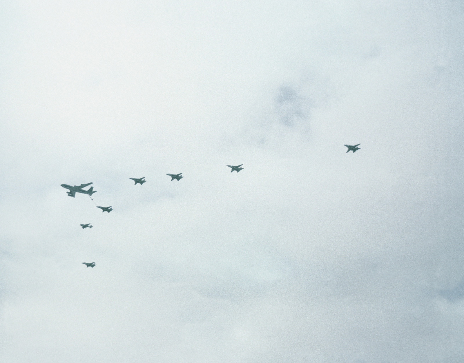 Six F-14A Tomcat and an A-6E Intruder aircraft from Carrier Air Wing 1 (CVW-1) conduct an in-flight refueling with an Air Force KC-135 Stratotanker aircraft while en route to their target during Operation Desert Storm. CVW-1 is deployed aboard the aircraft carrier USS AMERICA (CV 66).