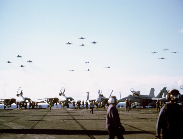Sixteen aircraft from Carrier Air Wing 1 (CVW-1) fly in fromation over the aircraft carrier USS AMERICA (CV 66) as the ship travels to the persian Gulf region for Operation Desert Shield. The aircraft include F-14A Tomcats, left; F/A-18C Hornets, upper center; A-6E Intruders, right; and an E-2C Hawkeye, an EA-6B Prowler, and two S-3B Vikings, lower center.