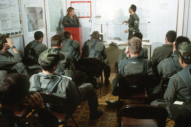 Squadron Commander LT. COL. Bruce Wright, at podium, brief members of the 614th Tactical Fighter Squadron on the first daylight attack of Operation Desert Storm.
