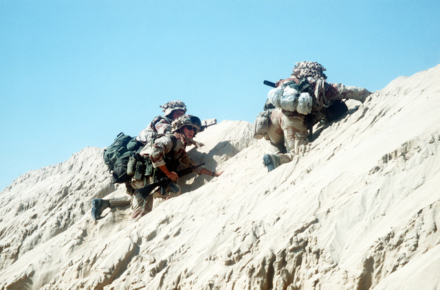 Three Marines climb the side of a berm as they move forward into attack positions during Operation DESERT STORM