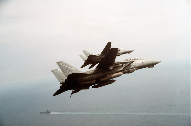Two Fighter Squadron 32 (VF-32) F-14A Tomcat aircraft bank toward the aircraft carrier USS JOHN F. KENNEDY (CV-67) during Operation Desert Storm