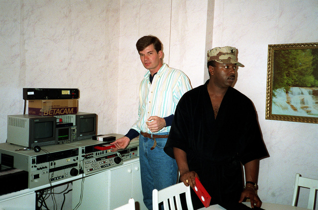 Two Navy journalists edit videotape at the Joint Information Bureau during Operation Desert Storm.