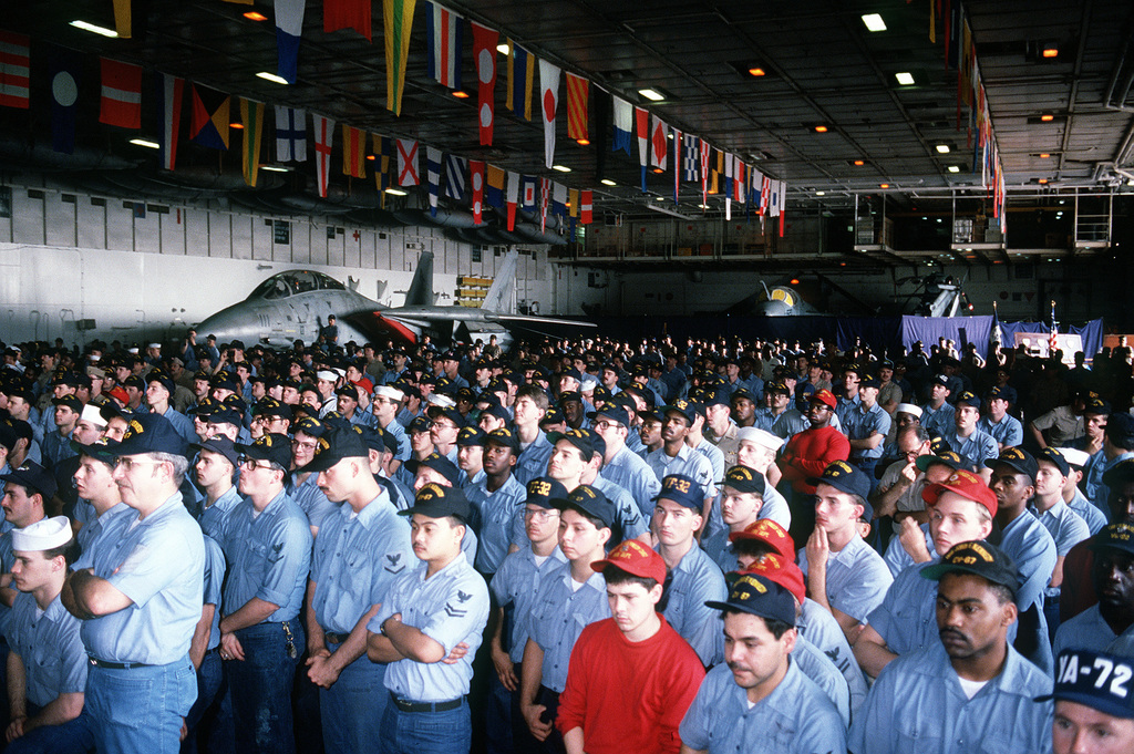 Crew members of the aircraft carrier USS JOHN F. KENNEDY (CV-67) listen to a speech by Vice President J. Danforth Quayle who is aboard the ship as part of a three-day visit with military forces deployed to the Middle East in support of Operation Desert Shield