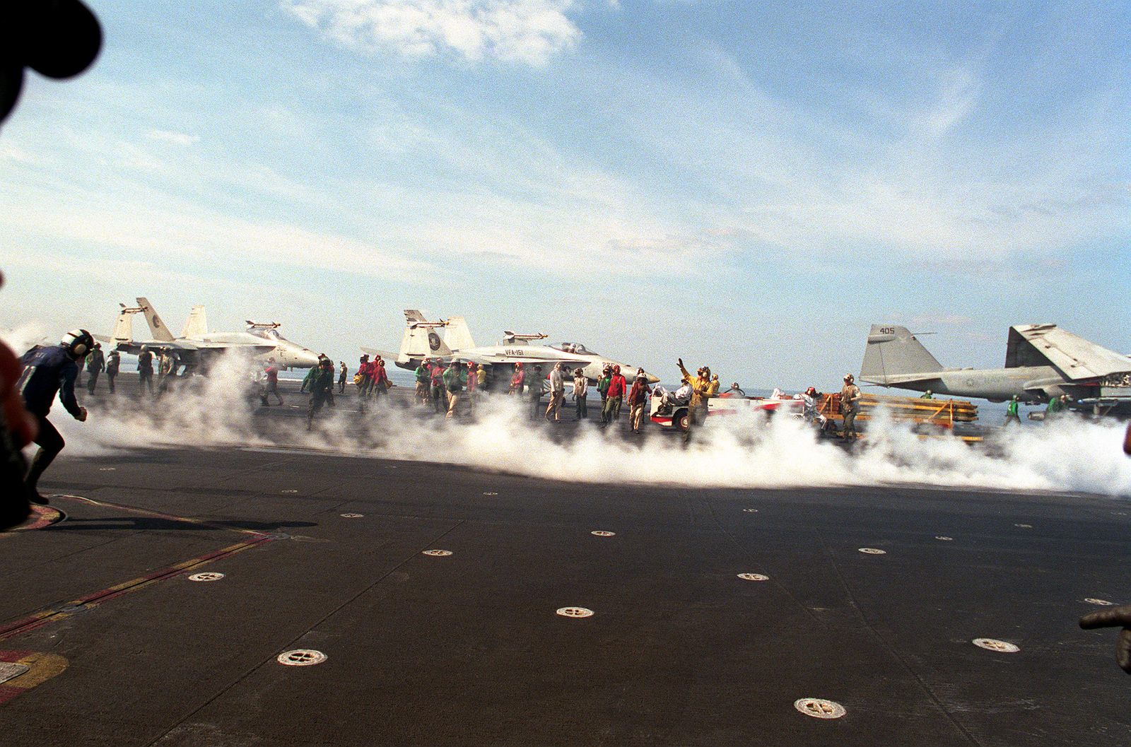 Steam rises from a catapult track on the flight deck of the aircraft carrier USS MIDWAY (CV-41) following the launch of an aircraft during Operation Desert Shield. In the background are F/A-18A Hornet aircraft from Strike Fighter Squadron 192 (VFA-192), left, and Strike Fighter Squadron 151 (VFA-151), center. An Attack Squadron 185 (VA-185) A-6E Intruder aircraft is at right