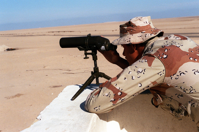 CPL. J.C. Johnson of A Company, 1ST Reconnaissance Battalion, scans the desert with a spotting scope during Operation Desert Shield