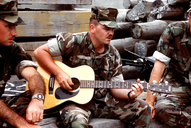 A Marine sergeant plays his guitar as he and the members of his unit wait on the pier. The Marines will be boarding U.S. Navy ships for transportation to the Persian Gulf region for Operation Desert Shield