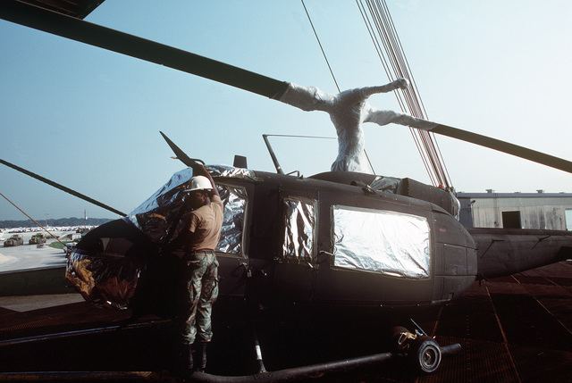 A member of the 101st Combat Support Group stands on the tow bar as a UH-1H Iroquois helicopter is moved along the loading ramp of the Saudi Arabian roll-on/roll-off cargo ship SAUDI HAIL. The unit's helicopters and other equipment are being loaded aboard the vessel for transportation to the Middle East in support of Operation Desert Shield