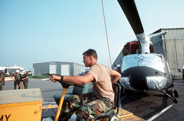 A member of the 1181st Transportation Terminal Unit tows a 101st Combat Support Group UH-1H Iroquois helicopter at a staging area. Helicopters and other equipment are being loaded aboard the Saudi Arabian roll-on/roll-off cargo ship SAUDI HAIL for transportation to the Middle East in support of Operation Desert Shield