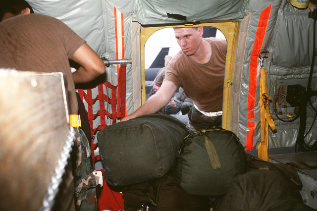 Airmen stack up mobility bags inside a KC-135A Stratotanker aircraft that will be carrying its cargo to the Persian Gulf region in support of Operation Desert Shield