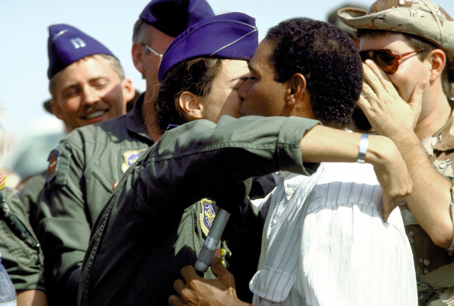 "An Air Force officer kisses Bryant Gumble of NBC's ""Today"" show during Gumble's visit to troops participating in Operation Desert Shield"