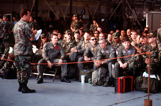 An airman calls the names of personnel waiting at a processing point as the 48th Tactical Fighter Wing prepares to deploy to Saudi Arabia for Operation Desert Shield