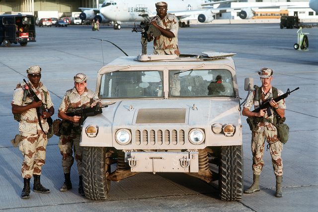 Members of a U.S. Central Command Air Forces (CENTAF) security police fire team gather around an M1038 High-Mobility Multipurpose Wheeled Vehicle (HMMWV) during Operation Desert Shield. The airmen are, from left: STAFF SGT. Rodney W. Link, AIRMAN Michael Grey, SGT. Shawn E. Roberts and TECH. SGT. Darrin C. Rice. Rice is a member of the 437th Security Police Squadron; the others are assigned to the 90th Security Police Group