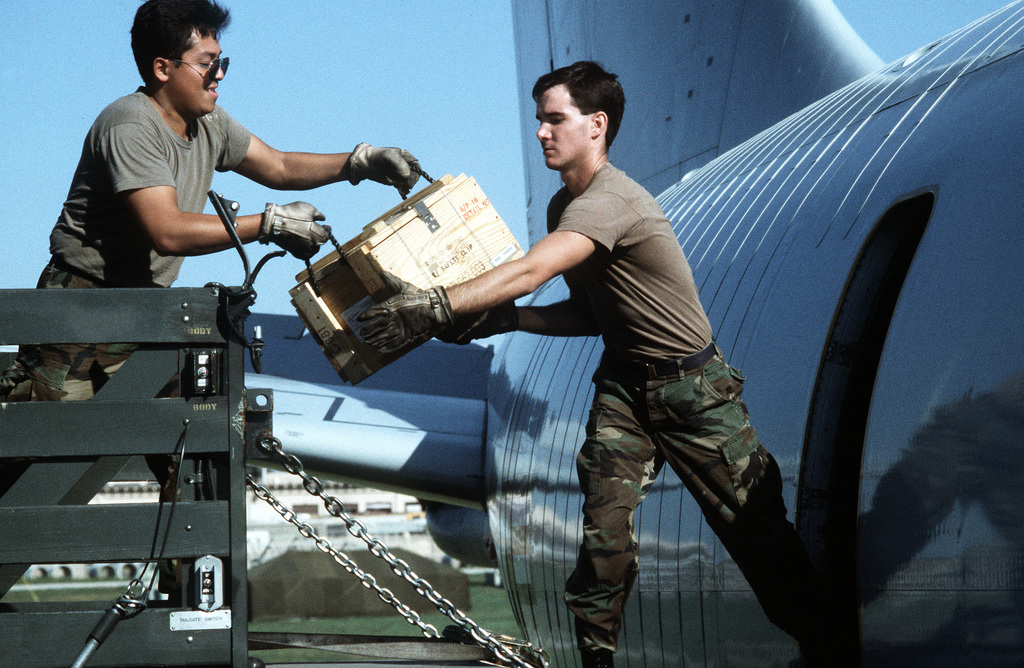 STAFF SGT. Robert Cruz, left, and AIRMAN 1ST Class Mark Barton load a case of hand grenades aboard a KC-135 Stratotanker aircraft bound for Saudi Arabia in support of Operation Desert Shield