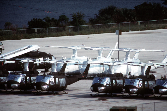 UH-1H Iroquois helicopters, some covered with protective wrappings, and a UH-60 Black Hawk (Blackhawk) helicopter line a staging area in preparation for loading aboard the Saudi Arabian roll-on/roll-off cargo ship SAUDI HAIL. The vessel will transport the equipment to the Middle East in support of Operation Desert Shield