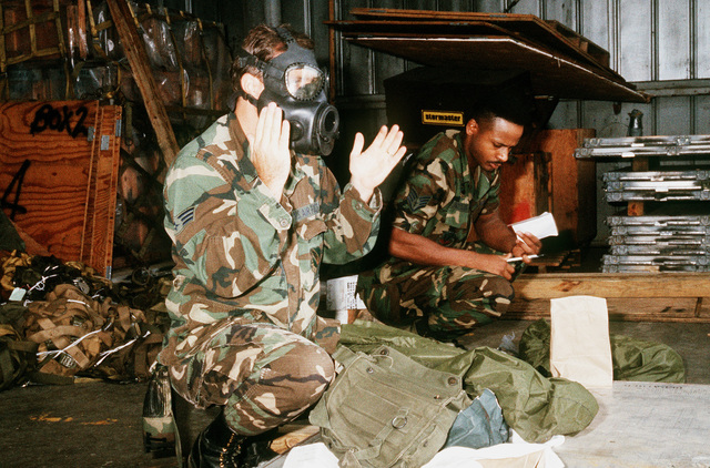 An air crew member tests the fit of an M-17 nuclear-biological-chemical mask as he and a companion prepare for deployment to Saudi Arabia in support of Operation Desert Shield