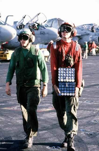 An aviation ordnanceman carries countermeasures dispenser systems across the flight deck of the aircraft carrier USS JOHN F. KENNEDY (CV-67). The systems will be mounted on aircraft in preparation for strikes on Iraqi targets at the onset of Operation Desert Storm