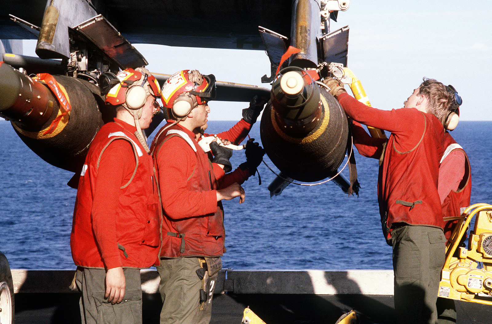 Aviation ordnanceman on the flight deck of the aircraft carrier USS JOHN F. KENNEDY (CV-67) mount a laser-guided bomb on an A-6E Intruder aircraft as it is fitted for strikes on Iraqi targets at the onset of Operation Desert Storm