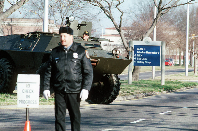 A policeman stands ready to check a visitor's identification as a V-100 Commando armored vehicle patrols in the background. The measures are being taken in an effort to strengthen base security following the outbreak of Operation Desert Storm hostilities between the Allied Forces and Iraq