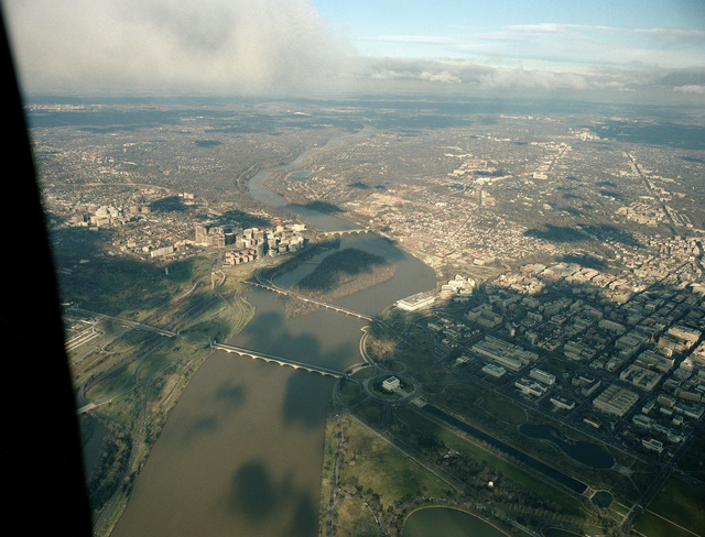 An aerial view of the Potomac River with the Arlington Memorial Bridge, foreground, and the Theodore Roosevelt Memorial Bridge crossing waterway into Virginia