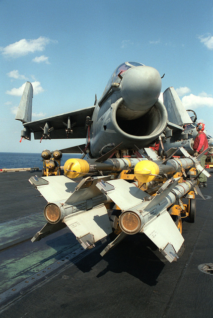 An ordnanceman prepares to load AIM-9 Sidewinder missiles, foreground, and Mark 82 500 lb. bombs on an Attack Squadron 72 (VA-72) A-7E Corsair II aircraft. The Corsair, based aboard the aircraft carrier USS JOHN F. KENNEDY (CV-67), will be used to make strikes against Iraqi targets during Operation Desert Storm