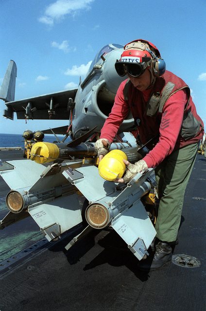 Aviation Ordnanceman 1ST Class Michael Gettys removes the cover from the tip of an AIM-9 Sidewinder missile prior to loading the ordnance on a A-7E Corsair II aircraft. The Corsair, based aboard the aircraft carrier USS JOHN F. KENNEDY (CV-67), is being armed for strikes against Iraqi targets during Operation Desert Storm