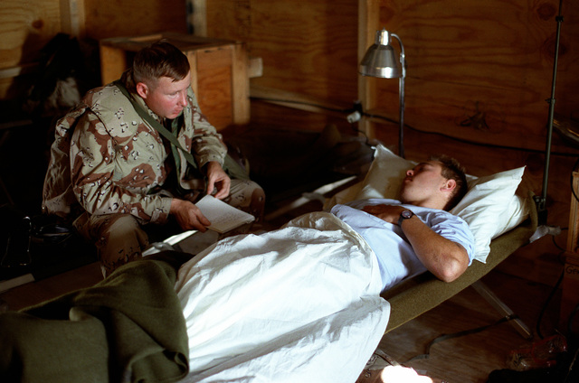 Hospital Corpsman 1ST Class Conners of the 1ST Reconnaissance Battallion, 1ST Marine Division, is interviewed from his bed in the 1ST Medical Battalion recovery room at Al Mishab. Conners became the first combat casualty of Operation Desert Storm when he was wounded in the shoulder