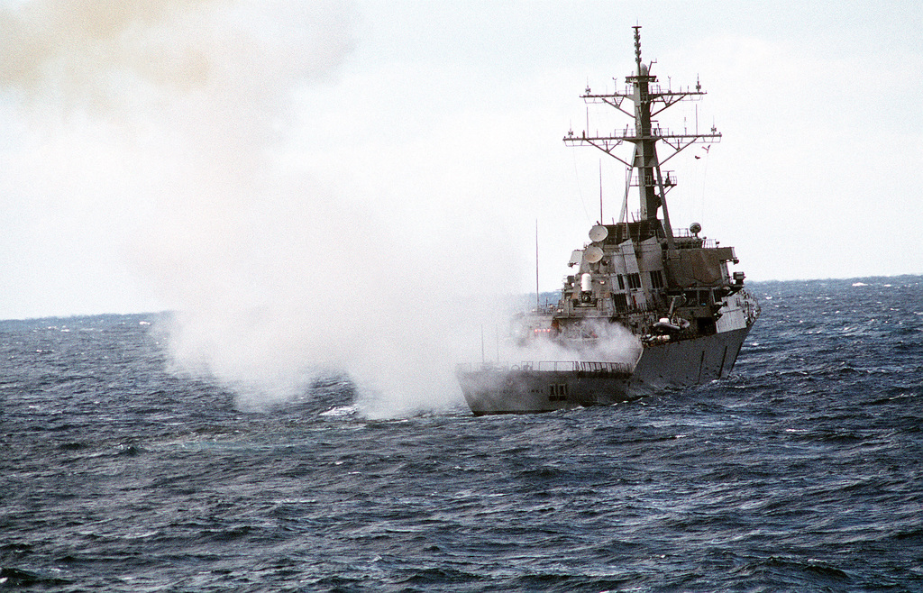 Smoke drifts away from stern of the guided missile destroyer ARLEIGHT BURKE (DDG-51) after a RIM-66C Standard SM-2 MR missile was fired from a cell in the ship's aft vertical launch system (VLS). The destroyer, now undergoing sea trials, is scheduled for commissioning on July 4, 1991