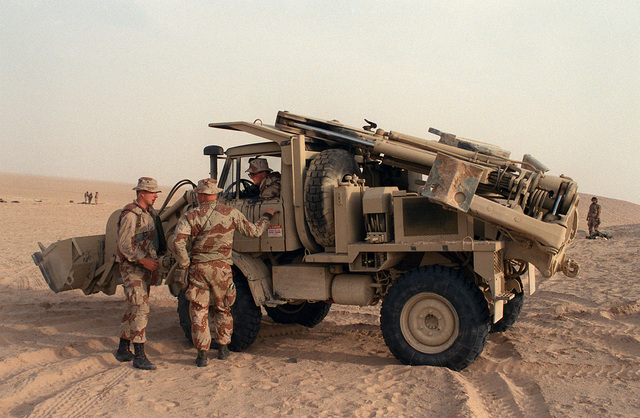 Two Marines from the 2nd Combat Engineer Battalion, 2nd Marine Division, talk to the driver of a Small Emplacement Excavator (SEE) as positions are prepared for Task Force Breach Alpha on Hill 231 during Operation Desert Storm.