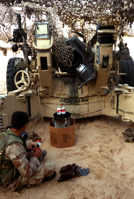 A Marine artilleryman takes a meal break next to his M-198 155mm howitzer during Operation Desert Storm