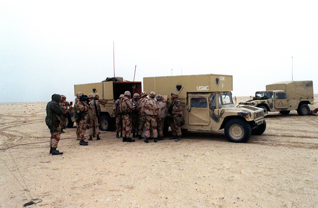 Marine artillerymen are briefed on an upcoming fire mission against Iraqi positions during Operation Desert Storm. They are standing next to a pair of M-998 series high-mobility multipurpose wheeled vehicles set up as command vehicles