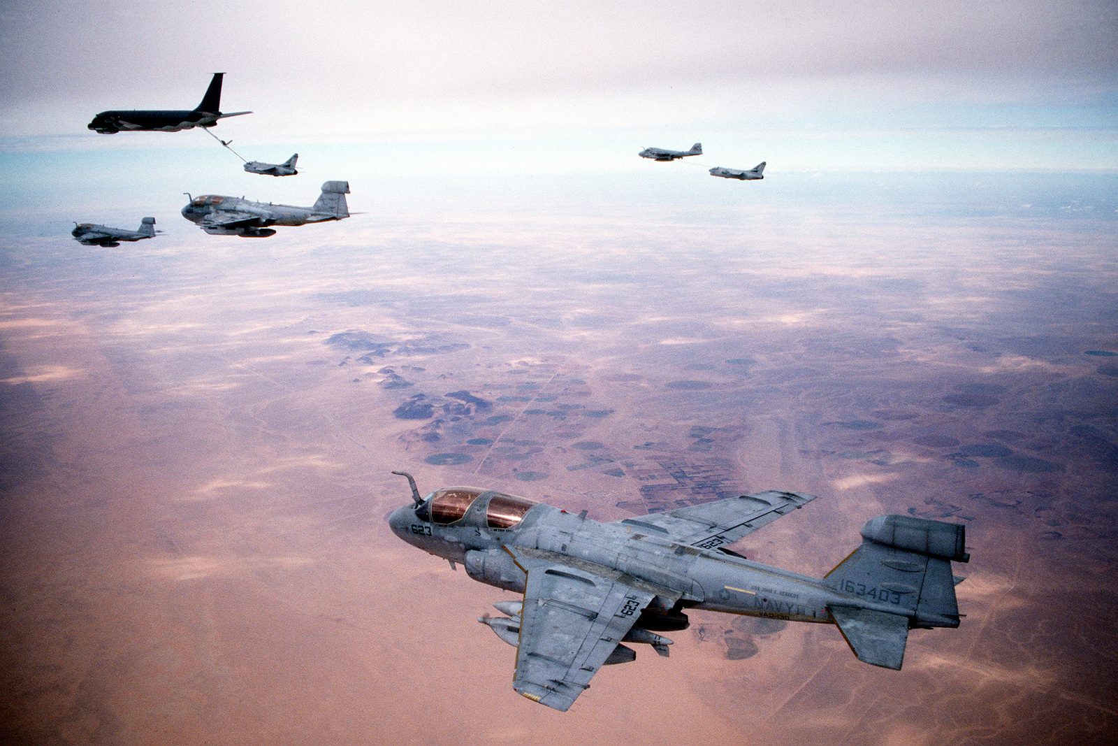 "Three Tactical Electronic Warfare Squadron 130 (VAQ-130) EA-6B Prowler aircraft wait as an Attack Squadron 72 (VA-72) A-7E Corsair aircraft is refueled by an Air Force KC-135E Stratotanker aircraft to refuel while en route to targets in Iraq during Operation Desert Storm. At upper right, an Attack Squadron 75 (VA-75) A-6E Intruder aircraft carrying a ""buddy store"" external fuel tank refuels a second Corsair aircraft. The Navy aircraft are based aboard the aircraft carrier USS JOHN F. KENNEDY (CV-67)"