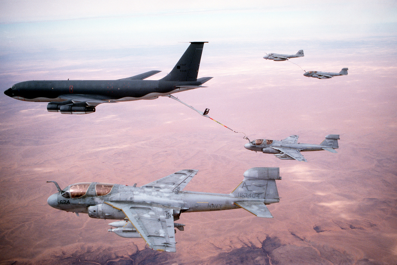 "Two Tactical Electronic Warfare Squadron 130 (VAQ-130) EA-6B Prowler aircraft rendezvous with a KC-135E Stratotanker aircraft to refuel while en route to targets in Iraq during Operation Desert Storm. At upper right, a third Prowler aircraft is refueled by an Attack Squadron 75 (VA-75) A-6E Intruder aircraft carrying a ""buddy store"" external fuel tank. VAQ-130 and VA-75 are based aboard the aircraft carrier USS JOHN F. KENNEDY (CV-67)"