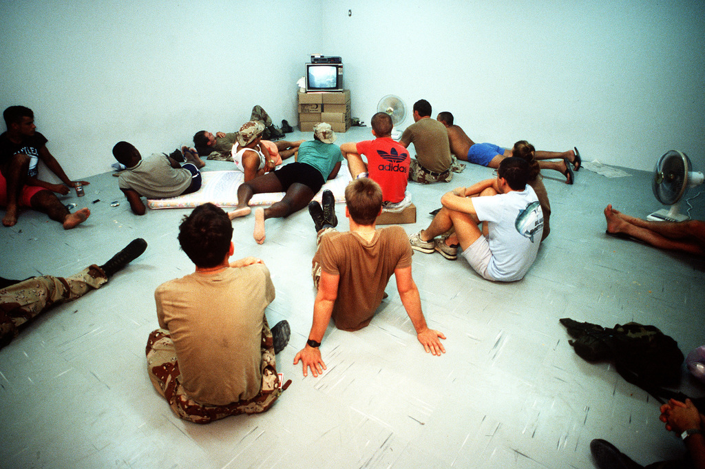U.S. military personnel take a break to watch television during Operation Desert Shield