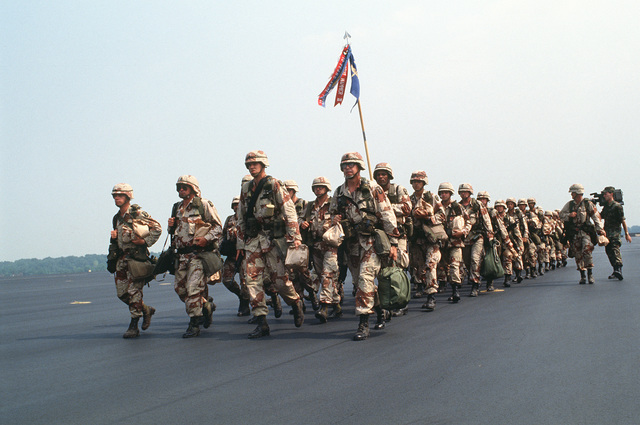 A company from the 101st Airborne Division (Air Assault) marches across the apron to board the aircraft that will carry the unit to Saudi Arabia for Operation Desert Shield